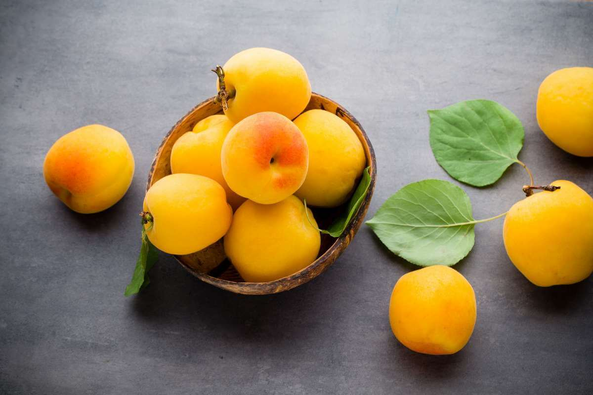 Apricot with leaves on wooden background