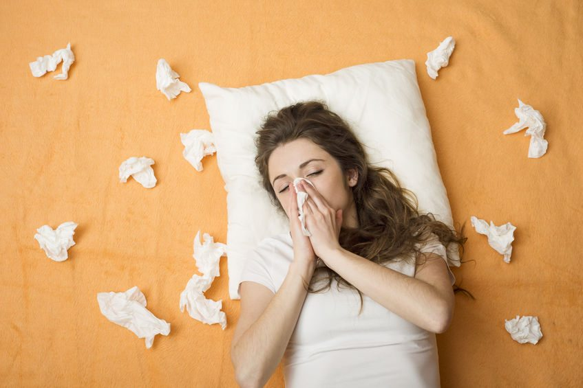 sick woman lying in bed with cold and flu